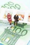 Figürchen, die auf Pillenorganisator mit 100 Euroanmerkungen sitzen Lizenzfreies Stockfoto