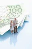 Figürchen, die 100 Euroanmerkungen bereitstehen Lizenzfreies Stockbild