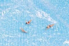Figürchen, die im Wasser zurück gerieben schwimmen Lizenzfreie Stockfotografie