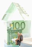 Figürchen, die vor Haus von 100 Euroanmerkungen sitzen Lizenzfreies Stockfoto