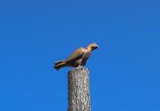 Figürchen eines Falken auf einem Stumpf eines Baums gegen den blauen Himmel Zahlen von den Tieren gemacht vom Holz woodcarving Stockfotografie