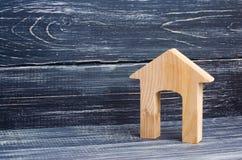 Figürchen eines Holzhauses mit einem großen Eingang auf einem Hintergrund von schwarzen Brettern Konzept von Immobilien, von Kauf Stockbild