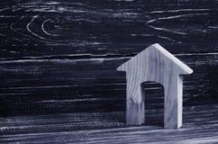 Figürchen eines Holzhauses mit einem großen Eingang auf einem Hintergrund von schwarzen Brettern Konzept von Immobilien, von Kauf Lizenzfreie Stockfotografie