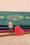 Figürchen neben einem Herzen, das auf Büchern steht stockfotos