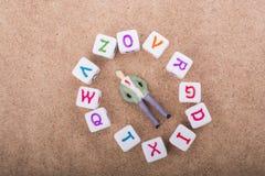 Figürchen und die bunten Alphabetbuchstabewürfel Lizenzfreie Stockfotografie