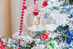 Figürchen von Rotwild in der Glasschüssel wiegt auf Weihnachtsbaum Stockbild