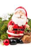 Figürchen von Santa Claus nahe der Niederlassung eines Weihnachtsbaums stockfotografie