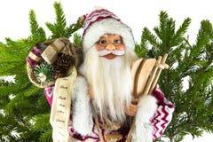 Figürchen von Santa Claus und von Tasche mit Geschenken auf dem Hintergrund von Stockfotografie