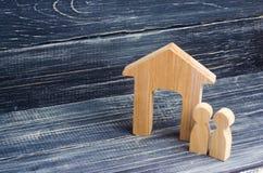 Figürchenholzhaus mit zwei Leuten nebeneinander auf einem Hintergrund von schwarzen Brettern Konzept von Immobilien, von Kauf und Stockfotografie