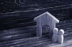 Figürchenholzhaus mit zwei Leuten nebeneinander auf einem Hintergrund von schwarzen Brettern Konzept von Immobilien, von Kauf und Stockbild