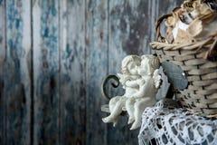 Figürchenliebesengel, die auf einer Bank sitzen Lizenzfreies Stockbild