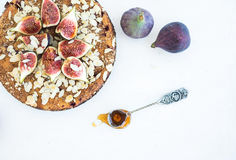 Fig cake with fresh figs, honey and almond flakes on white Stock Images
