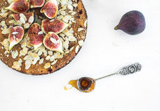 Fig cake with fresh figs, honey and almond on white Royalty Free Stock Images