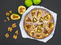 Fig cake with fresh figs and walnuts on black Stock Images