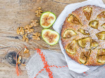 Fig cake with fresh figs and walnuts on a rought wood surface Stock Photos