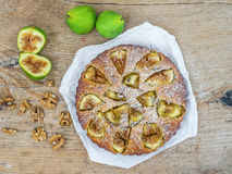 Fig cake with fresh figs and walnuts on a rought wood surface Royalty Free Stock Photos