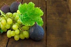 Fig. en druiven op houten lijst Stock Foto's