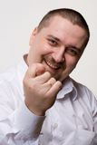 Fig gesture. Portrait of man in white shirt showing fig gesture Stock Images