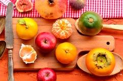 Fig., granaatappel, avocado, appelen en mandarins (mandarijnen) op ruwe achtergrond Stilleventhema Stock Afbeeldingen