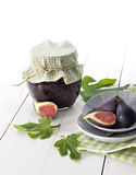 Fig jam. Black mission fig jam and fresh figs with leaves on old white wooden table Royalty Free Stock Photos