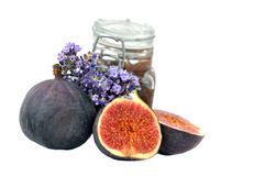 Fig jam with fresh fruits. A glas of fig jam on white background with fresh fruits and lavender royalty free stock photography