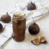 Fig jam in glass jar and fresh figs on white wooden table, side view. Closeup royalty free stock photography