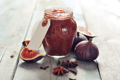 Fig jam. In a glass jar with  fresh figs on wooden background Stock Photos