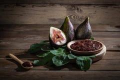 Fig.jam met fig., vijgebladen en houten lepel met jam op houten achtergrond stock foto