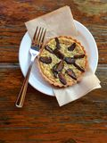 Fig and pistachio tart at pastry shop. A fig and pistachio (fruit and nut) tart on a napkin and white plate shot top-down from above with a fork on a wooden Stock Photography
