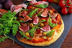 Fig pizza with bacon, green pimiento olives, rocket and basil leaves.  Royalty Free Stock Photography