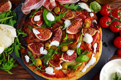 Fig pizza with bacon, green pimiento olives, rocket and basil leaves.  Stock Photo