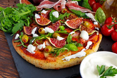 Fig pizza with bacon, green pimiento olives, rocket and basil leaves.  Stock Image