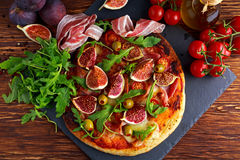 Fig pizza with bacon, green pimiento olives, rocket and basil leaves.  Royalty Free Stock Photo