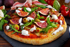 Fig pizza with bacon, green pimiento olives, rocket and basil leaves.  Royalty Free Stock Photos