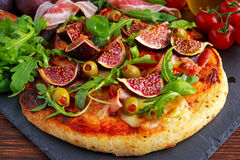 Fig pizza with bacon, green pimiento olives, rocket and basil leaves.  Royalty Free Stock Image
