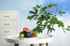 Fig plant and plate with ripe fruits. On table indoors stock images