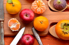 Fig, pomegranate, apple and mandarines (tangerines) on rough background Stock Photo