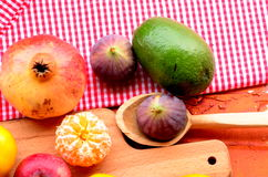 Fig, pomegranate, apple and mandarins (tangerines) on rough background Royalty Free Stock Photos