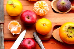 Fig, pomegranate, apple and mandarins (tangerines) on rough background Stock Image