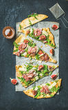 Fig, prosciutto, arugula and sage flatbread pizza cut into pieces Stock Photography