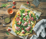 Fig, prosciutto, arugula and sage flatbread pizza with rose wine. Fig, prosciutto, arugula and sage flatbread pizza with glass of rose wine on wax paper over Stock Photography