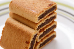 Fig Rolls. A close up of a stack of five fig rolls on a plate with a white background Stock Images