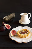 Fig tart. Creamy almond and fresh fig tart on black wooden table with creamer, tart molds and fresh black mission figs royalty free stock photo