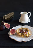 Fig tartelette. Half-eaten creamy almond and fresh fig tartelette on black wooden table with creamer, tartelette molds and fresh black mission figs royalty free stock images