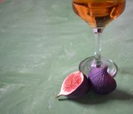 Fig and wineglass. On a gree background Royalty Free Stock Images