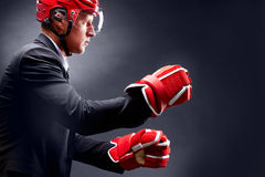 Fight. Portrait of young businessman in suit and hockey helmet and gloves fighting stock images