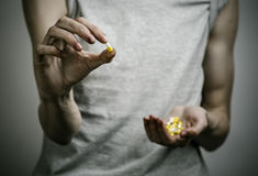The fight against drugs and drug addiction topic: addict holding a narcotic pills on a dark background. In studio Royalty Free Stock Photography