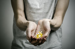The fight against drugs and drug addiction topic: addict holding a narcotic pills on a dark background. In studio Royalty Free Stock Images