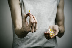 The fight against drugs and drug addiction topic: addict holding a narcotic pills on a dark background. In studio Royalty Free Stock Image