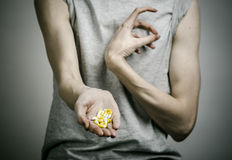 The fight against drugs and drug addiction topic: addict holding a narcotic pills on a dark background. In studio Stock Photography